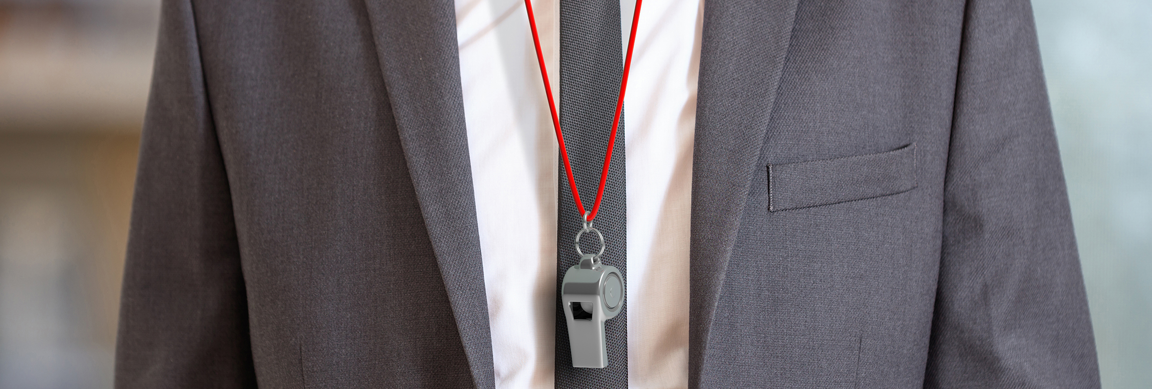 A close up of a man wearing a suit. He is a career coach and there is a whistle with a red lanyard around his neck.